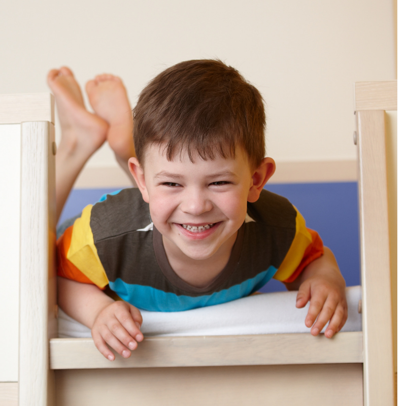 Little kid laughing on top of bunk bed