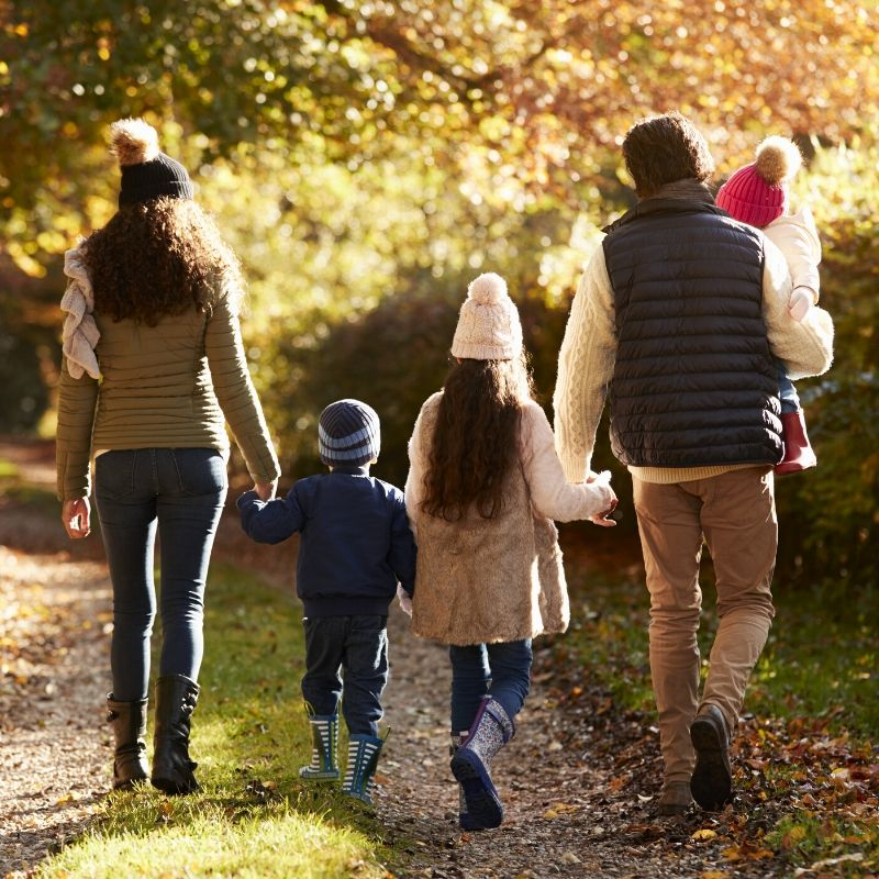 Family walking down a wooded path